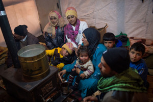 Members of a Syrian refugee family huddle around a stove inside their shelter in Lebanon's Bekaa Valley. Photo: UNHCR/A. McConnell