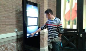 Un visitatore ricerca informazioni sul totem touch screen