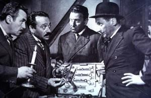 Umberto Spadaro nelle vesti dello scassinatore Natale Papini di Livorno (secondo da sinistra), e Paolo Stoppa in quelle del professore suo aiutante fiorentino ultimo a destra, mettono a punto l'armamentario per scassinare la cassaforte dell'Evidenzbüro austriaco di Zurigo. Scena del film Senza bandiera di Lionello De Felice del 1951